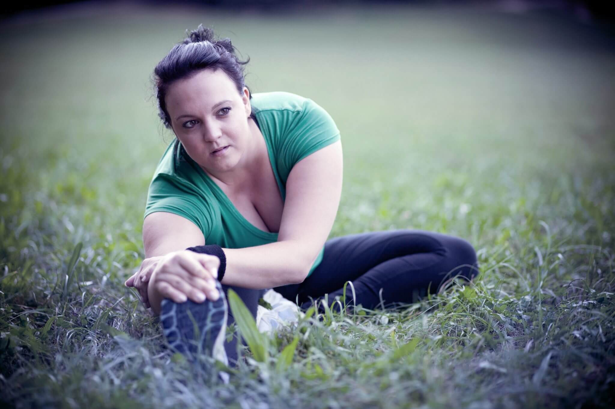 Image of plus sized woman stretching in a park