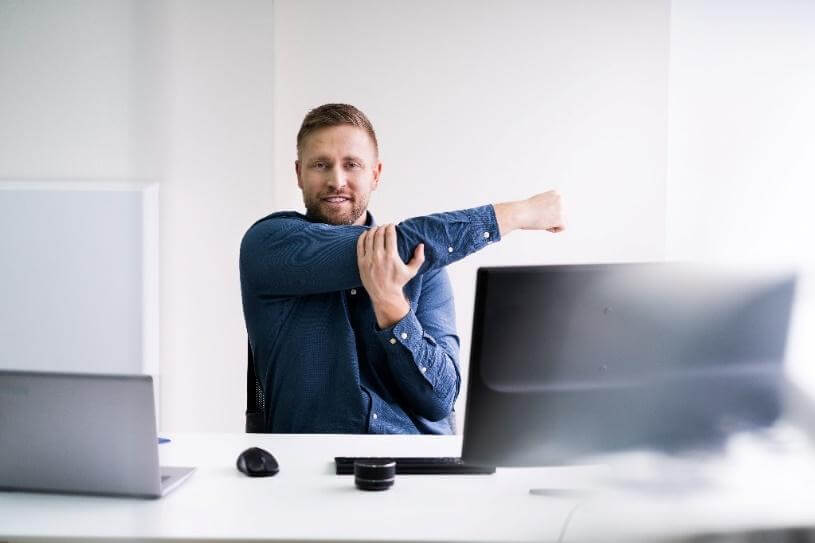 A man sitting in front of his computer, stretching his arm across his body