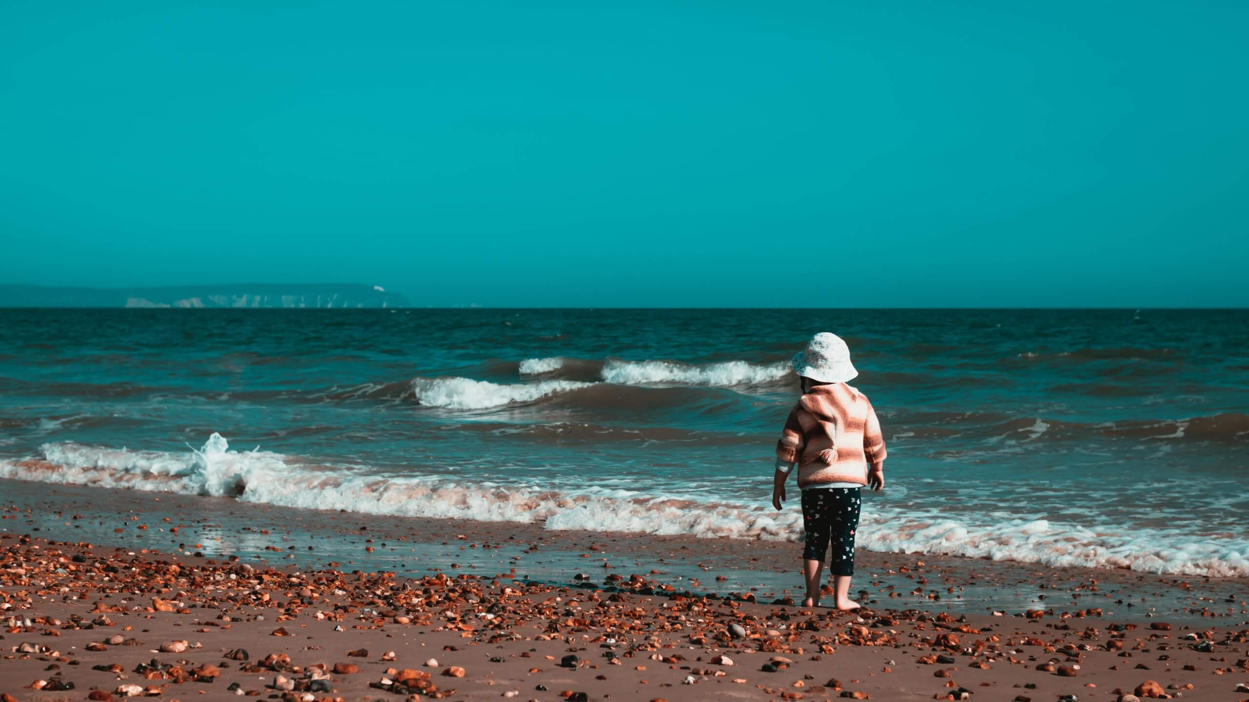 small child standing by the ocean