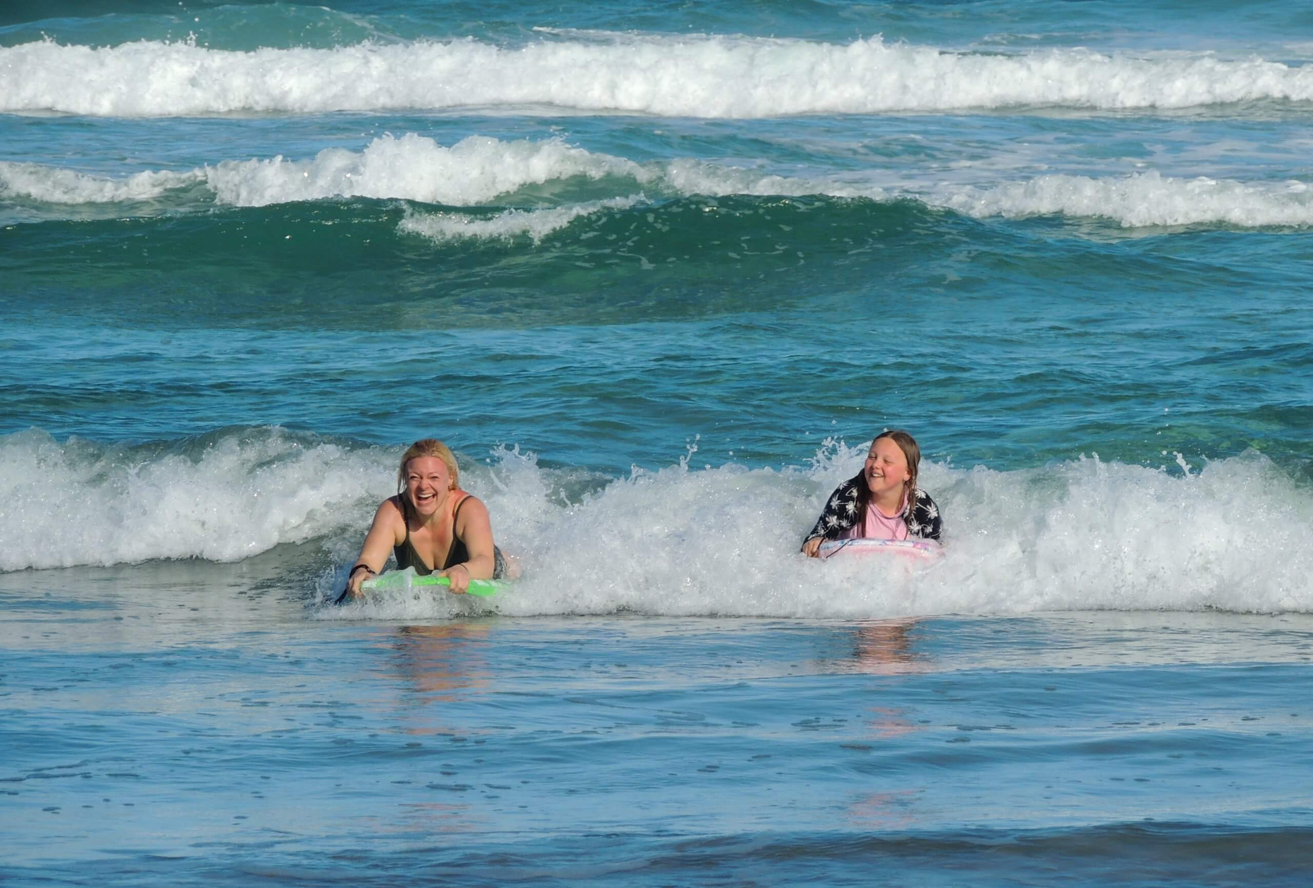 Mother and daughter body boarding